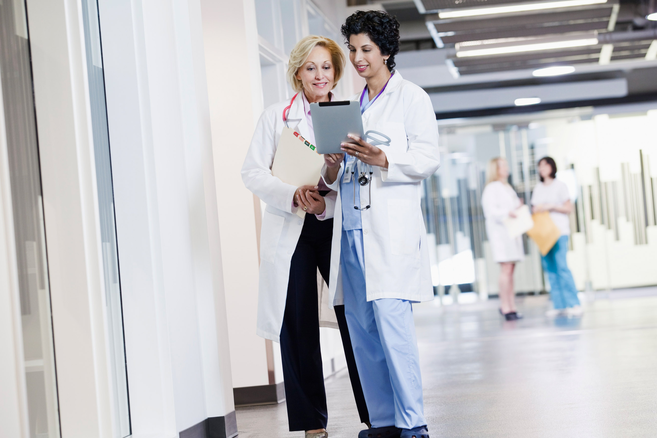 Two female doctors talking in corridor --- Image by © Kate Kunz/Corbis